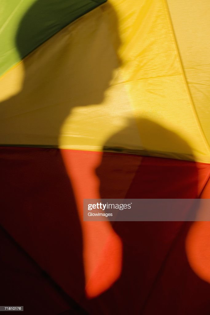 Close-up of the shadow of two people on a gay pride flag