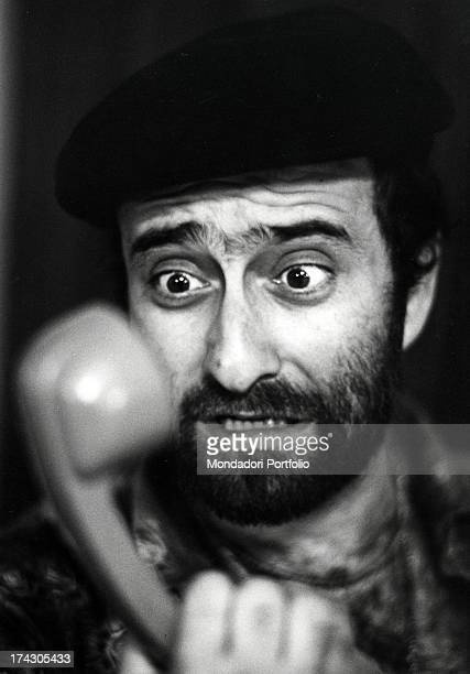 Closeup of the singer Lucio Dalla looking at a telephone receiver by keeping his eyes wide Sorrento Italy 1972