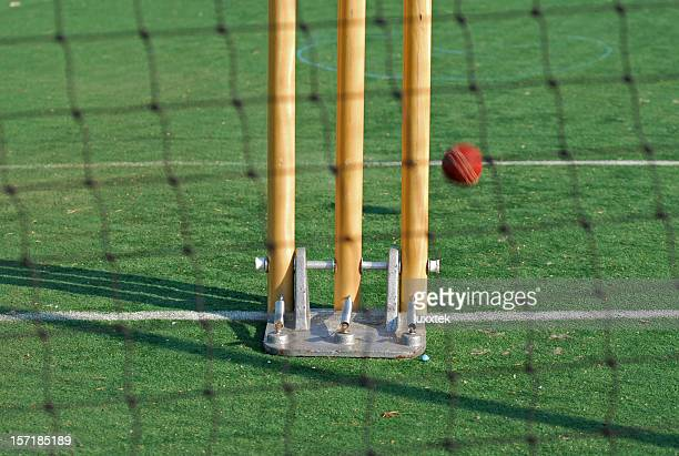 Close-up of the wickets and red Cricket ball on green pitch
