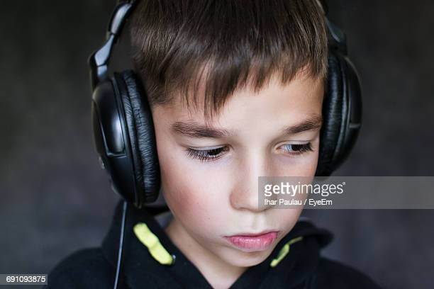 Close-Up Of Thoughtful Boy Listening Music In Headphones