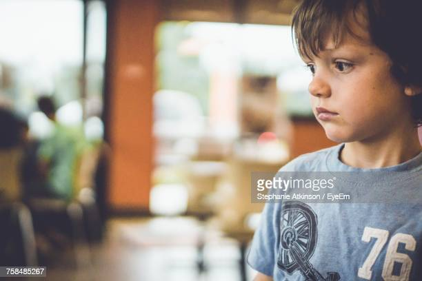 Close-Up Of Thoughtful Boy Looking Away While Standing In Cafe