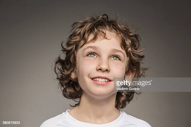 Close-up of thoughtful boy over gray background