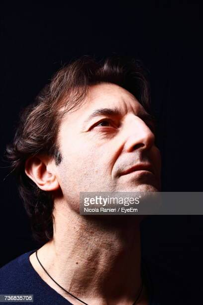 Close-Up Of Thoughtful Man Looking Up In Darkroom