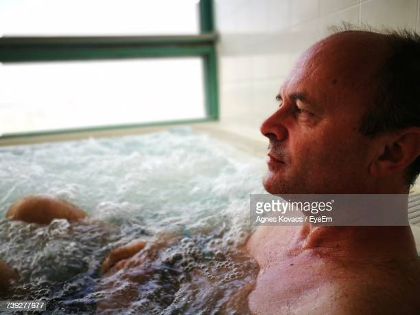 Close-Up Of Thoughtful Man Relaxing In Bathtub