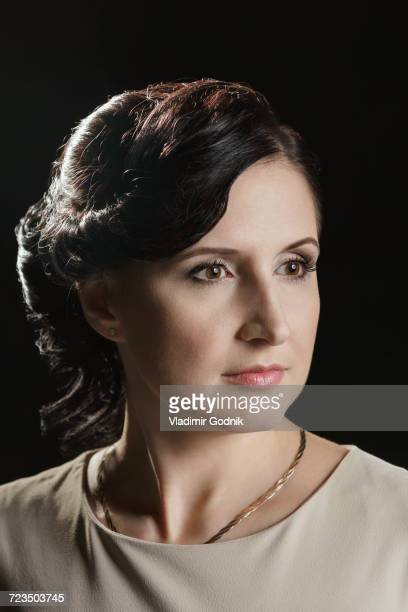 Close-up of thoughtful mid adult woman against black background