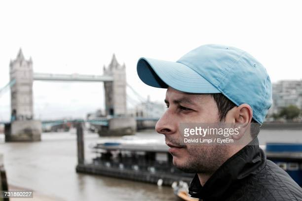 Close-Up Of Thoughtful Young Man Looking Away With Tower Bridge Over River Thames In Background