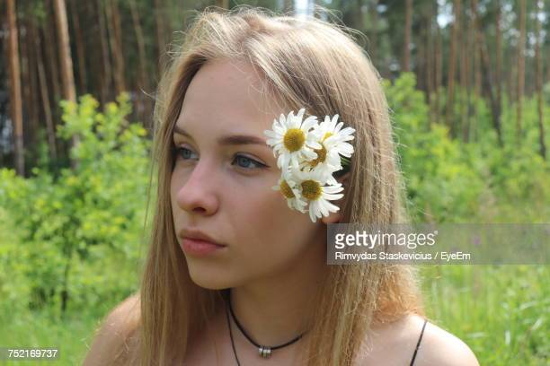 Close-Up Of Thoughtful Young Woman Wearing Flowers While Standing In Park