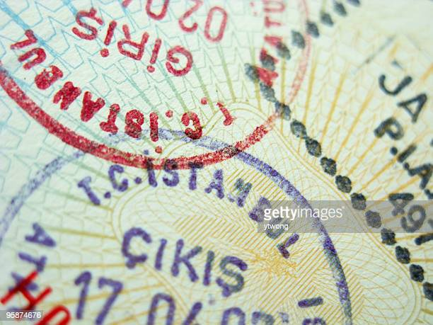 A close-up of three passport stamps for different countries