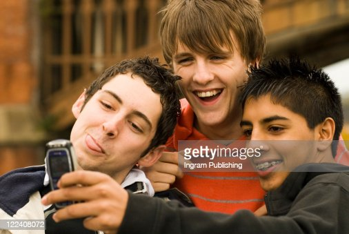 Close-up of three teenage boys taking a photograph of themselves with a mobile phone : Foto de stock