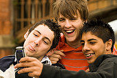 Close-up of three teenage boys taking a photograph of themselves with a mobile phone