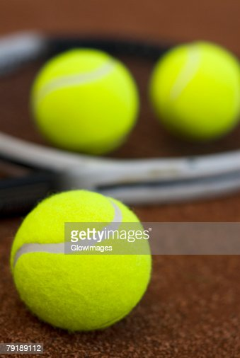 Close-up of three tennis balls and a racket in a court : Stock Photo