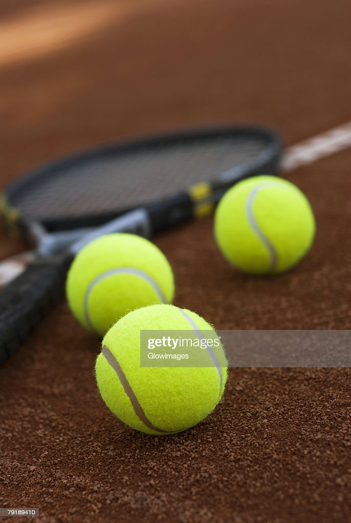 Close-up of three tennis balls and a racket in a court : Foto de stock