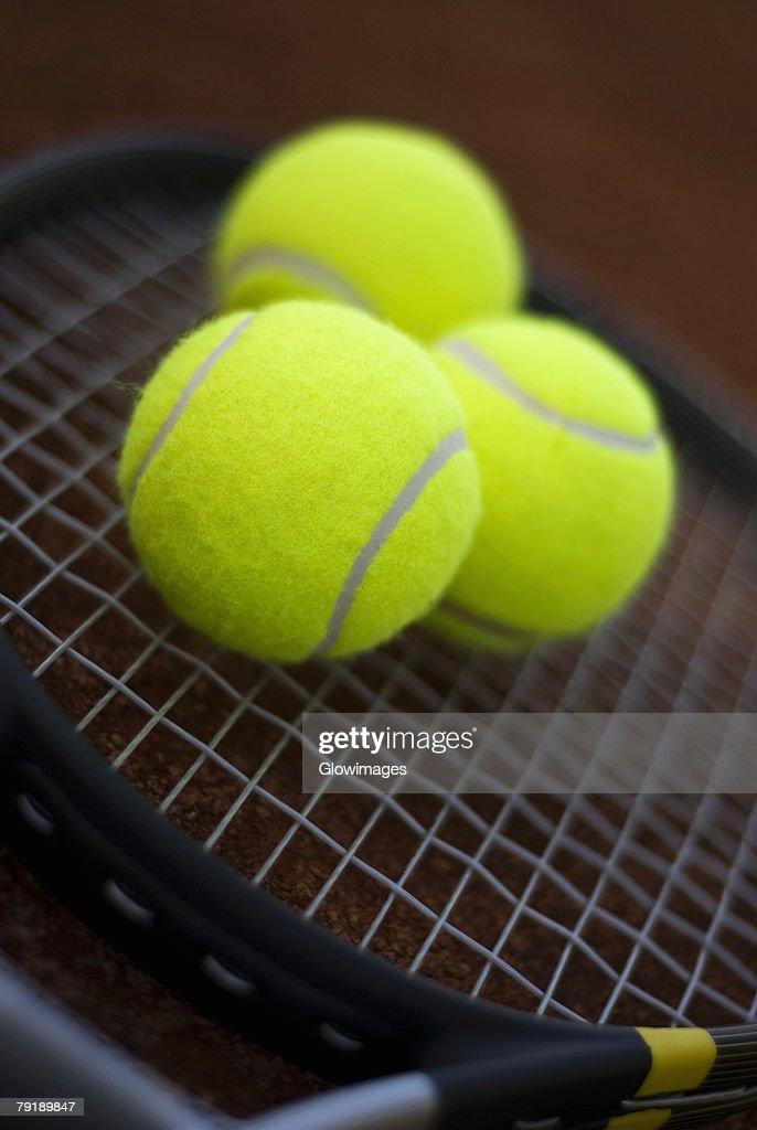 Close-up of three tennis balls on a tennis racket : Foto de stock