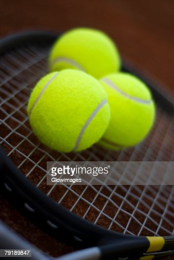 Close-up of three tennis balls on a tennis racket : Foto de stock