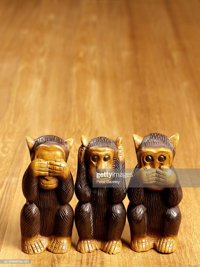 Close-up of three wooden monkey statues on table : Stock Photo