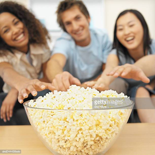 Close-up of three young people eating popcorn
