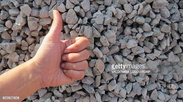 Close-up of thumbs up in front of stone