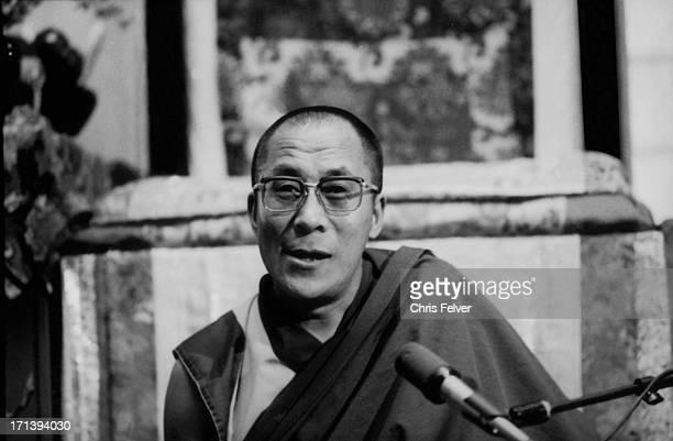 Closeup of Tibetan Buddhist leader the 14th Dalai Lama as he sits behind a microphone 1980