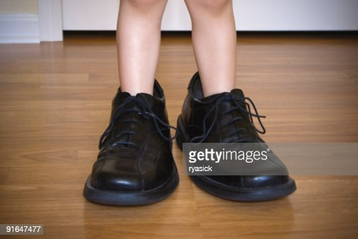 Closeup of Toddlers Legs Wearing Large Adult Shoes
