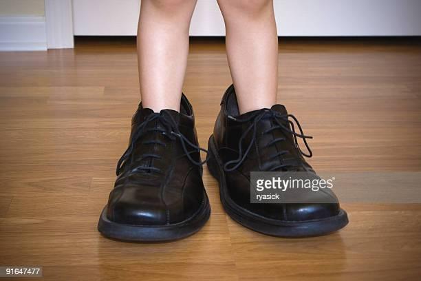 幼児レッグスのクローズアップの大人の靴を着て、反対