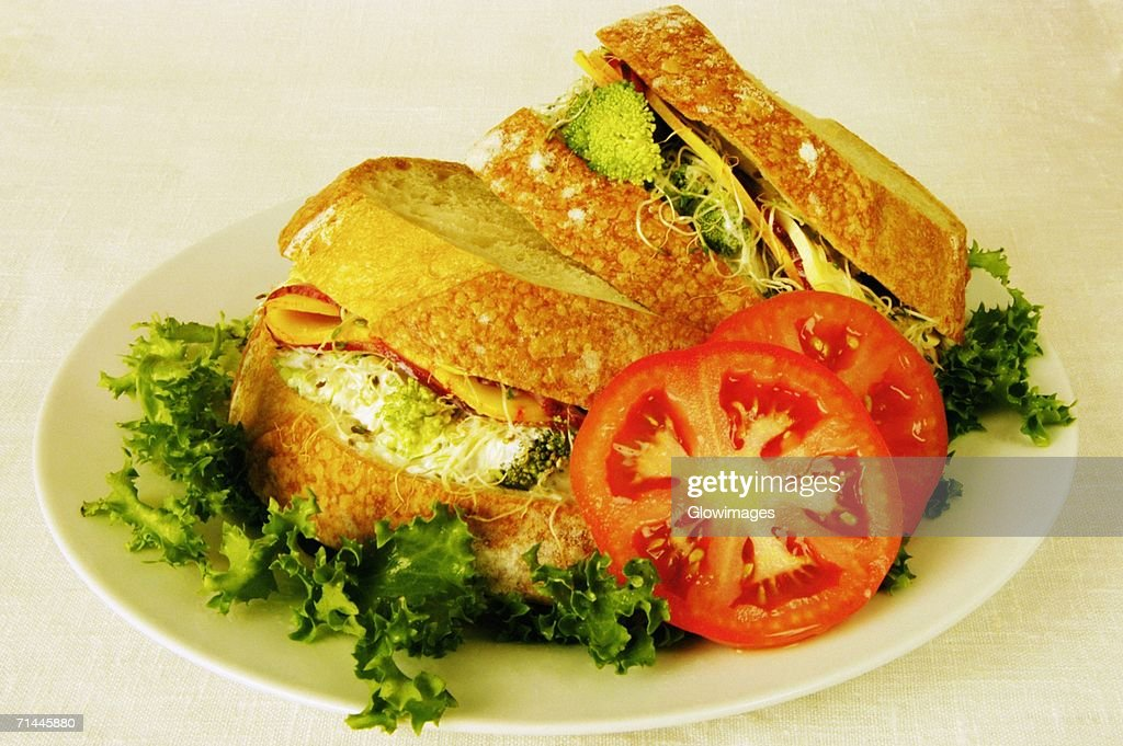 Close-up of tomato slices and sandwiches on a plate : Stock Photo