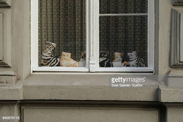 Close-Up Of Toy Cats On Window Sill
