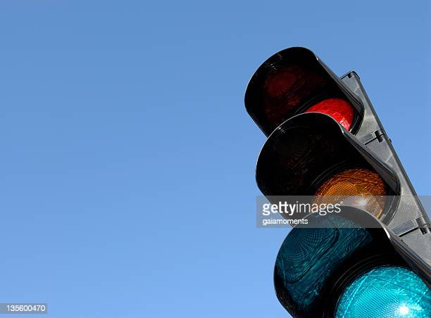 Close-up of traffic lights against blue sky