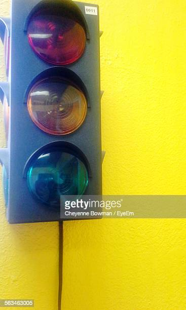 Close-Up Of Traffic Signal Over Yellow Background