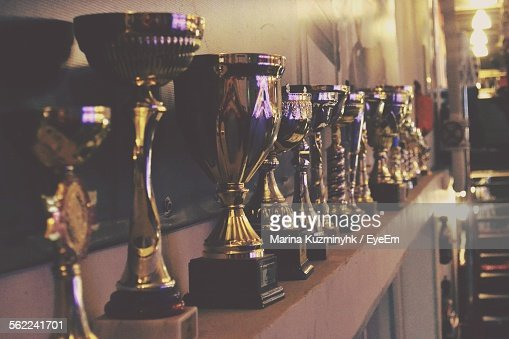 Close-Up Of Trophy On Shelf Against Wall