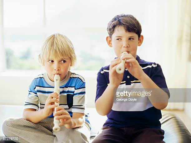 Close-up of two boys playing the recorder