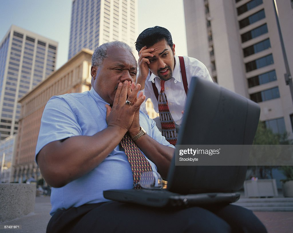 close-up of two businessmen shocked at the data on a laptop screen : Stock Photo