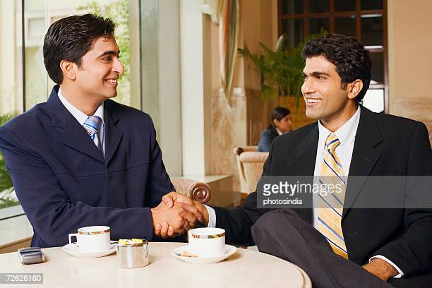 Close-up of two businessmen sitting in a cafeteria