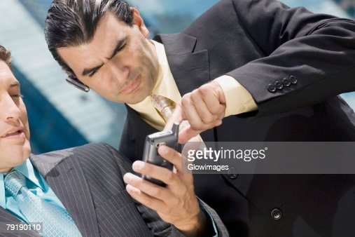 Close-up of two businessmen using a palmtop : Foto de stock