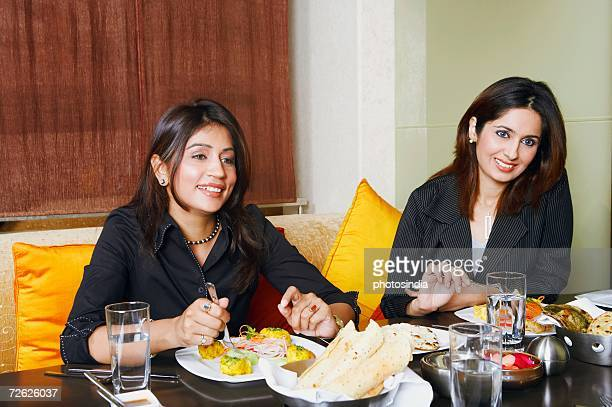 Close-up of two businesswomen eating in a restaurant