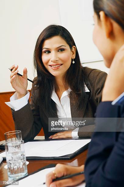 Close-up of two businesswomen sitting in a meeting