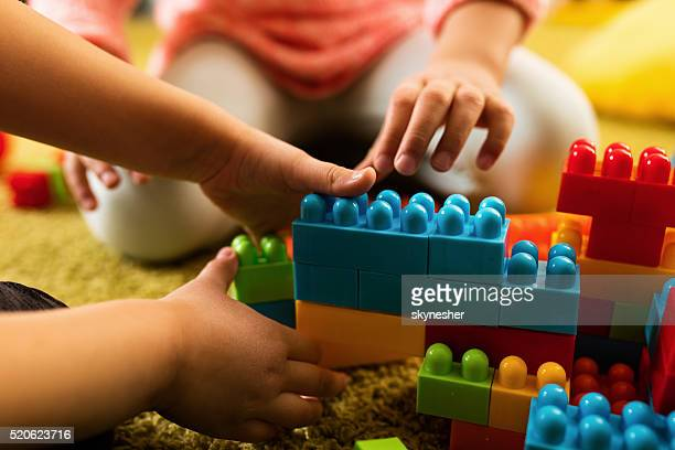 Close-up of two children playing with toy blocks.