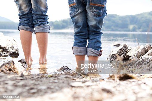 Close-up of two children standing at lakeshore