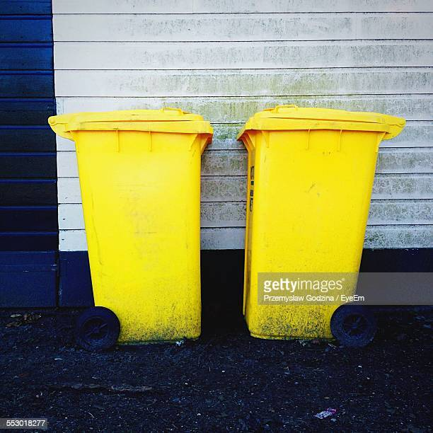 Close-Up Of Two Garbage Bins Against Wall