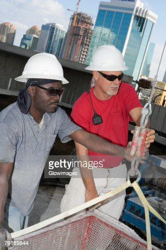 Close-up of two male construction workers working at a construction site : Stock Photo