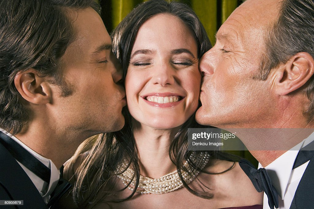 Close-up of two men kissing a young woman