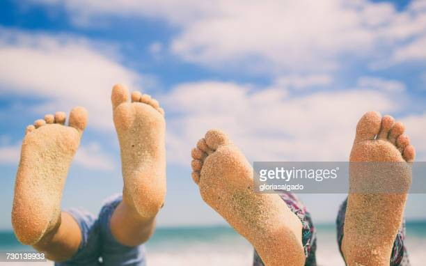 Close-up of two pairs of feet on beach covered in sand