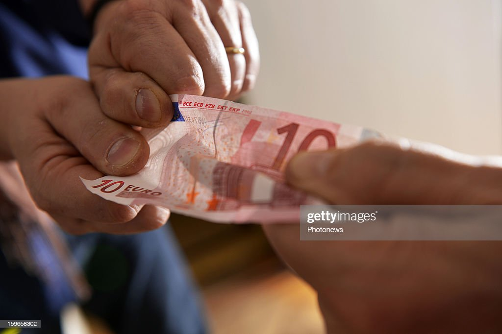 Close-up of two people's hands fighting for a ten euros note on January 14, 2013 in Brussels,Belgium.