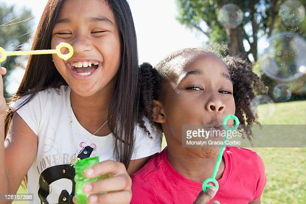Close-up of two smiling girls (10-12) blowing bubbles outdoors