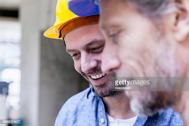 Close-up of two smiling men on construction site