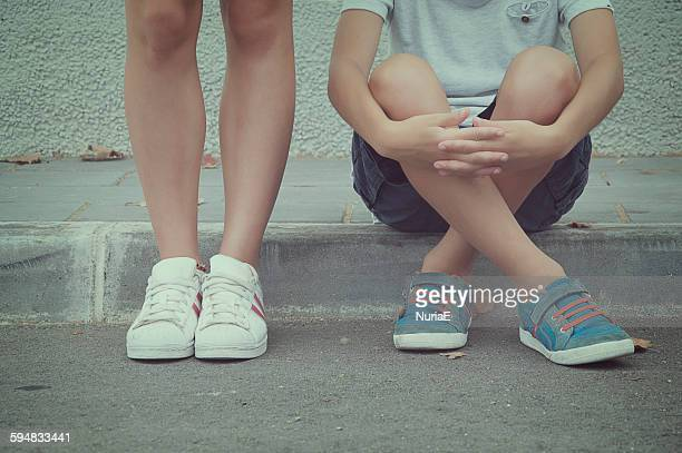Close-up of two teenagers sitting and standing in the street