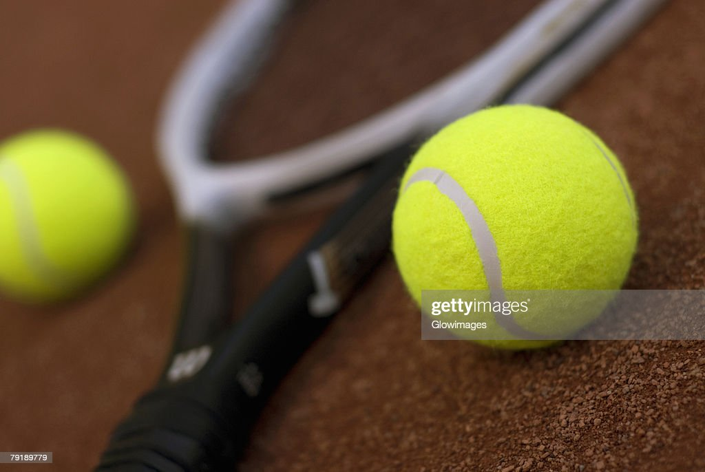 Close-up of two tennis balls and a tennis racket : Stock Photo