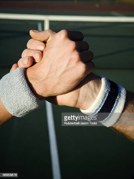 Close-up of two tennis players shaking hands