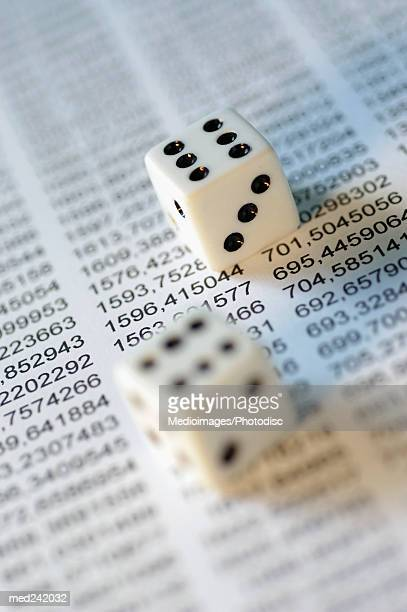 Close-up of two white dice kept on printed paper