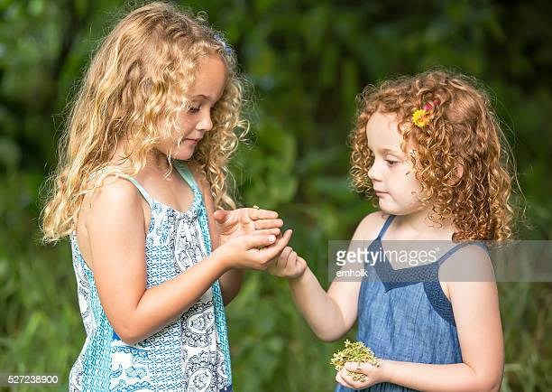 Close-Up of Two Young Girls With Monarch Butterfly Caterpillar