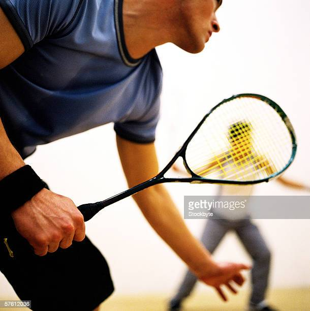Close-up of two young men playing squash (blurred)